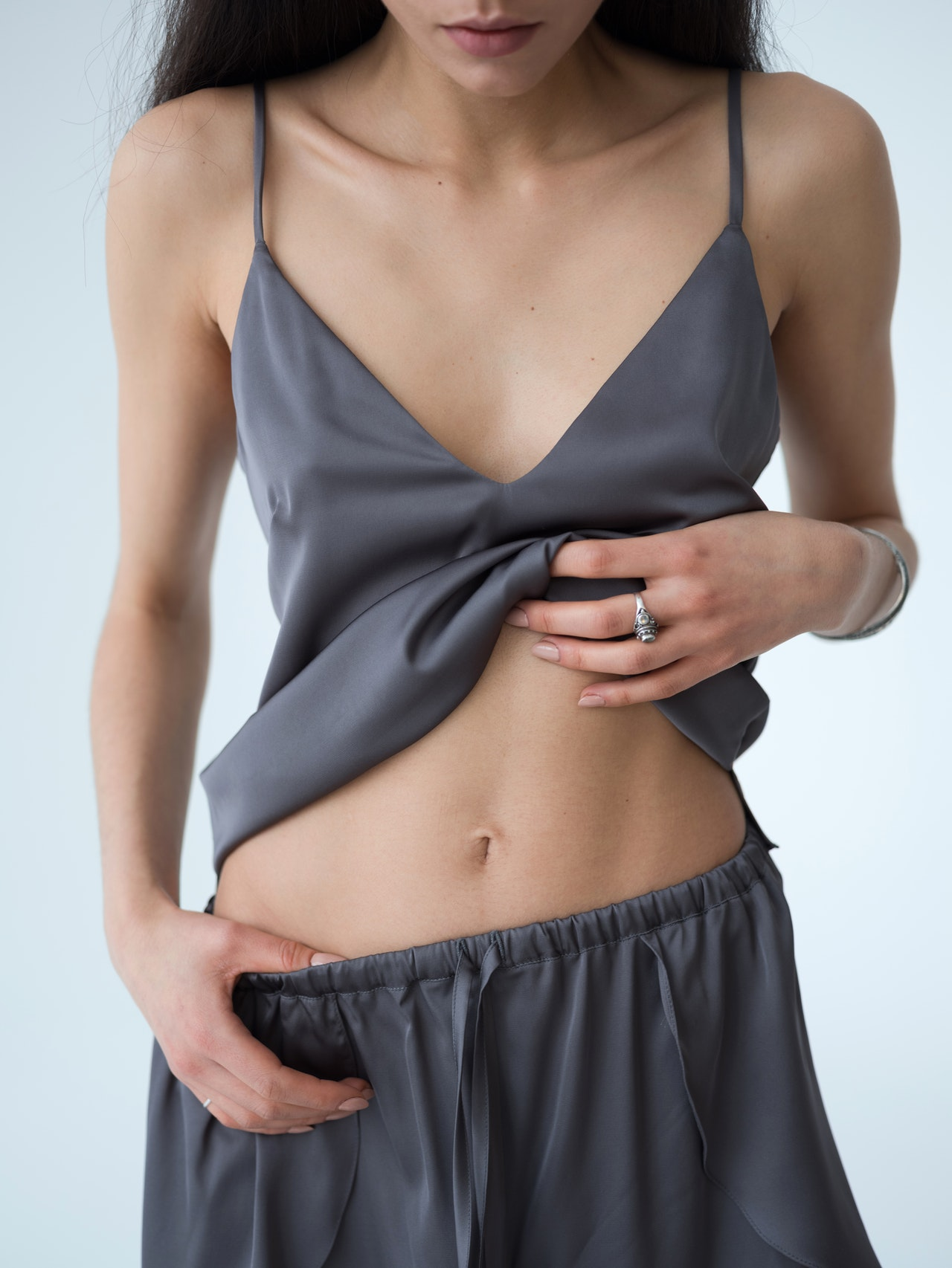 Girl in grey clothing showing stomach