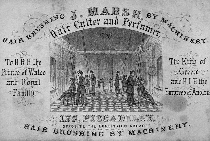 Визитная карточка парикмахера и парфюмера Дж. Марша, XIX век. Все четыре парикмахера на иллюстрации обслуживают клиентов с помощью вращающихся щеток, спускающихся с потолка. Надпись внизу: «Аппаратное расчесывание волос». Источник: Сьюзан Дж. Винсент, «Волосы: иллюстрированная история»