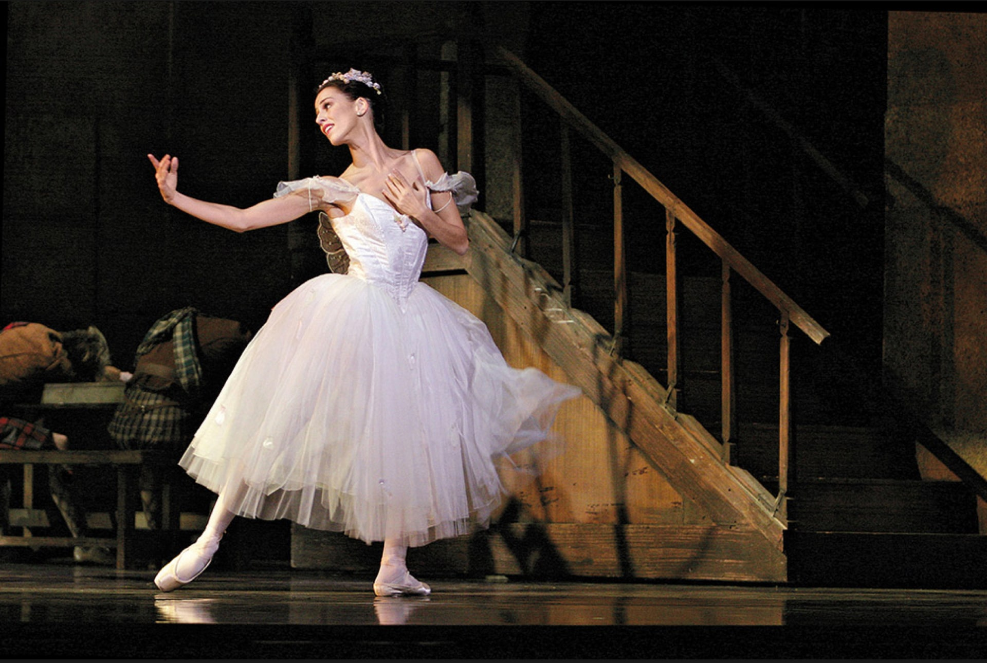 Ballerina in white dress gestures longingly beside wooden staircase.
