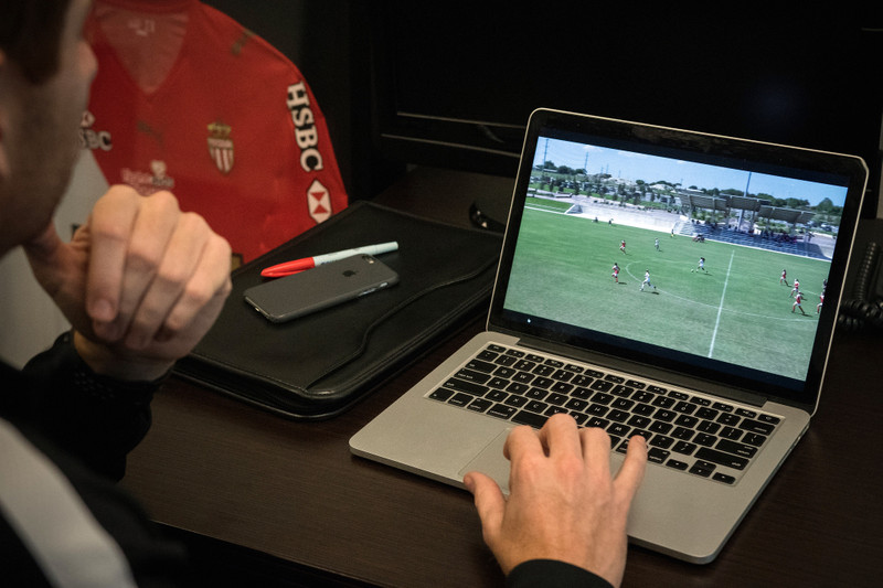 Analyst watches soccer video on laptop