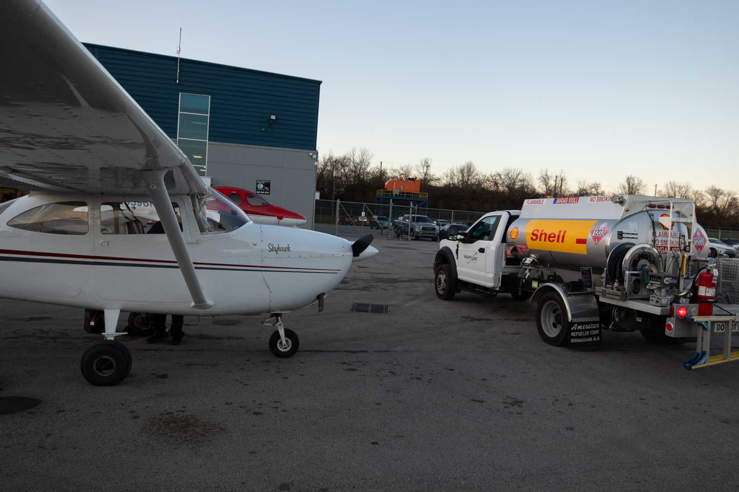 An aircraft parked on the airport ramp being fueled.
