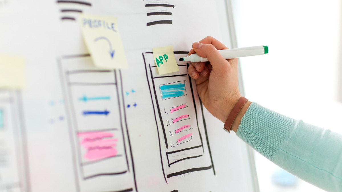 Close-up on UX designer's hands, writing on a stick note over a whiteboard mockup