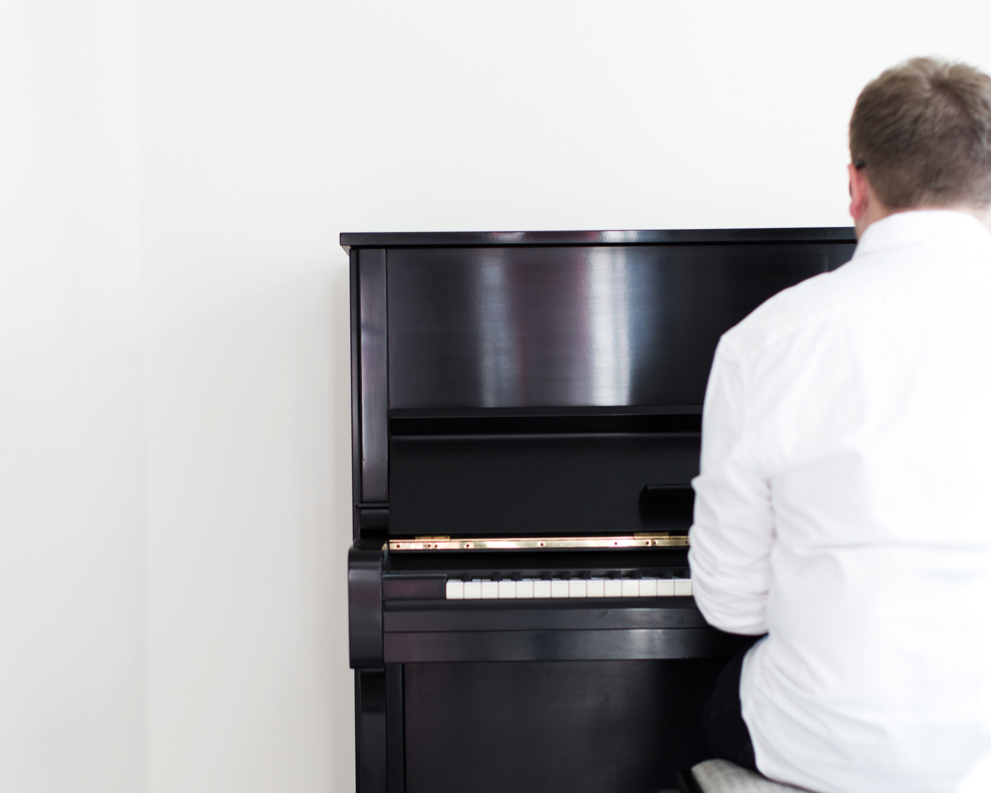 Jack Watkins playing a black Yamaha upright piano in a simple, light filled white space
