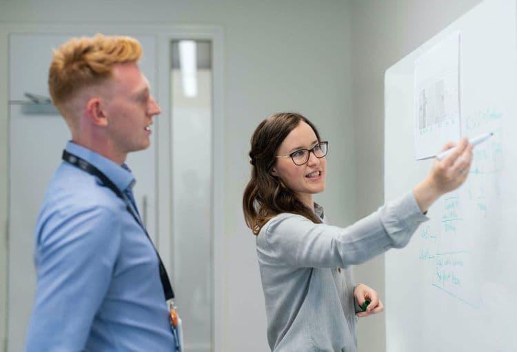 Beraterin erklärt Optimierung mit auf Whiteboard