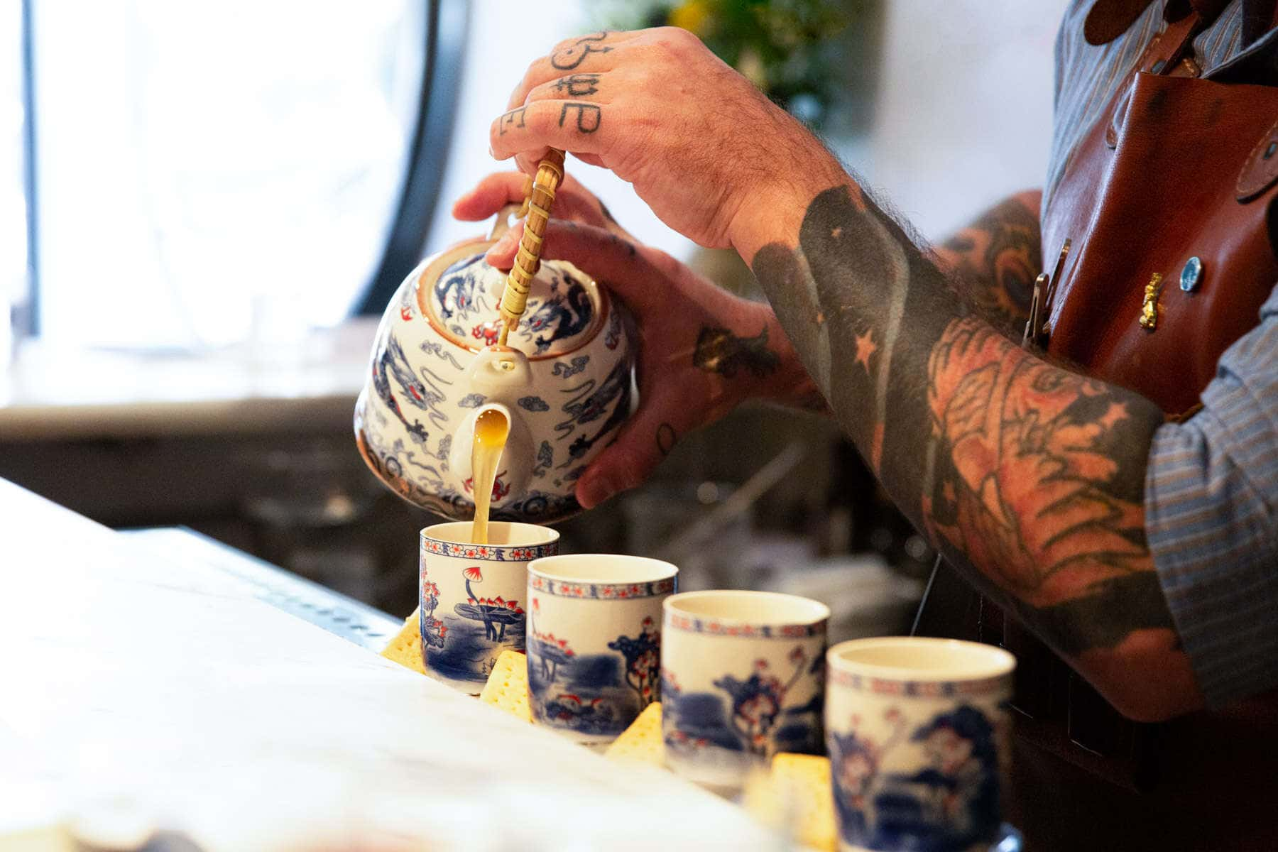 tea-cocktail-being-pored-by-tattooed-bartender