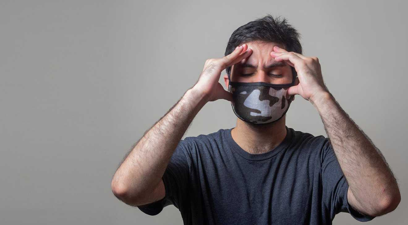 person on grey background wearing a mask and holding hands on temples