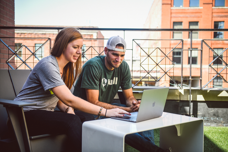 Two Hudl employees sat at a laptop