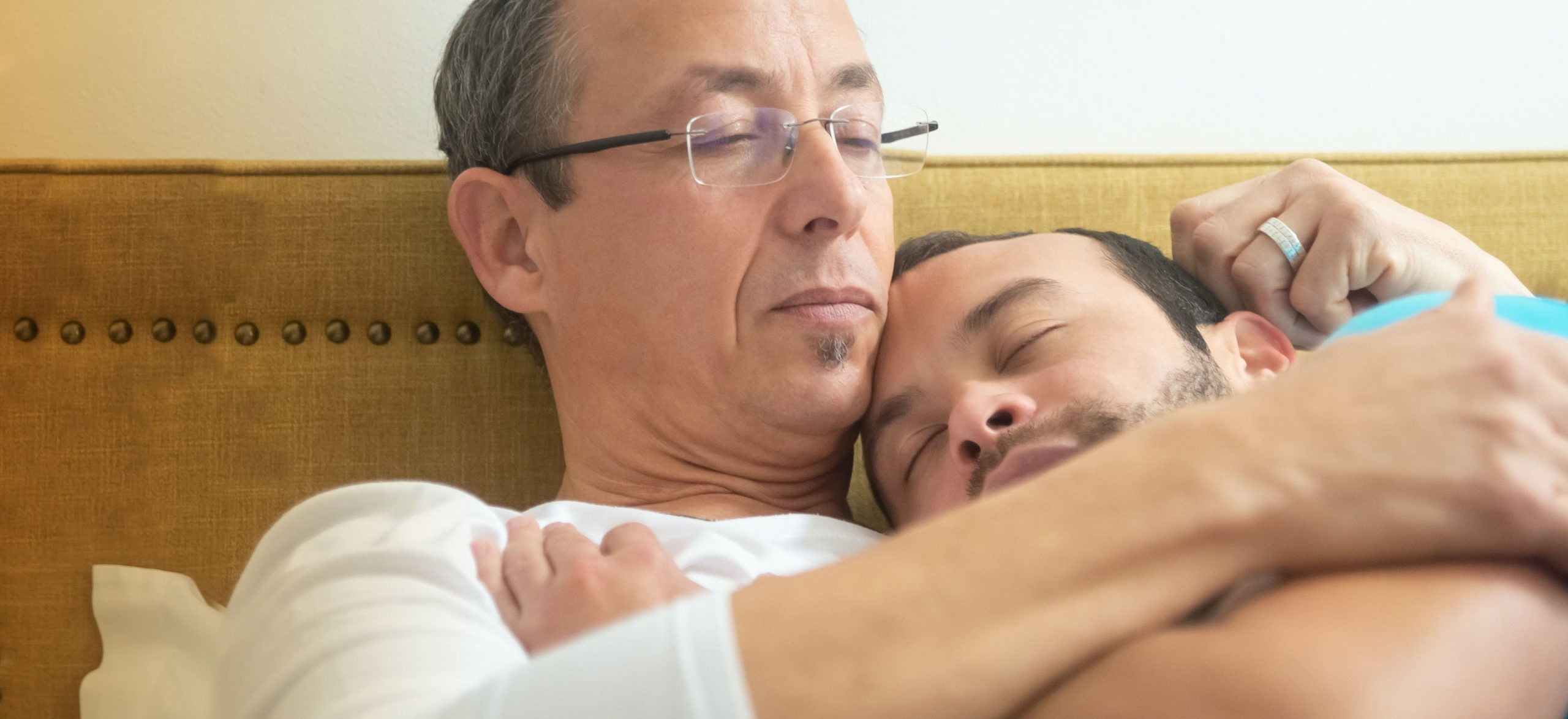 Two men embrace in a bed
