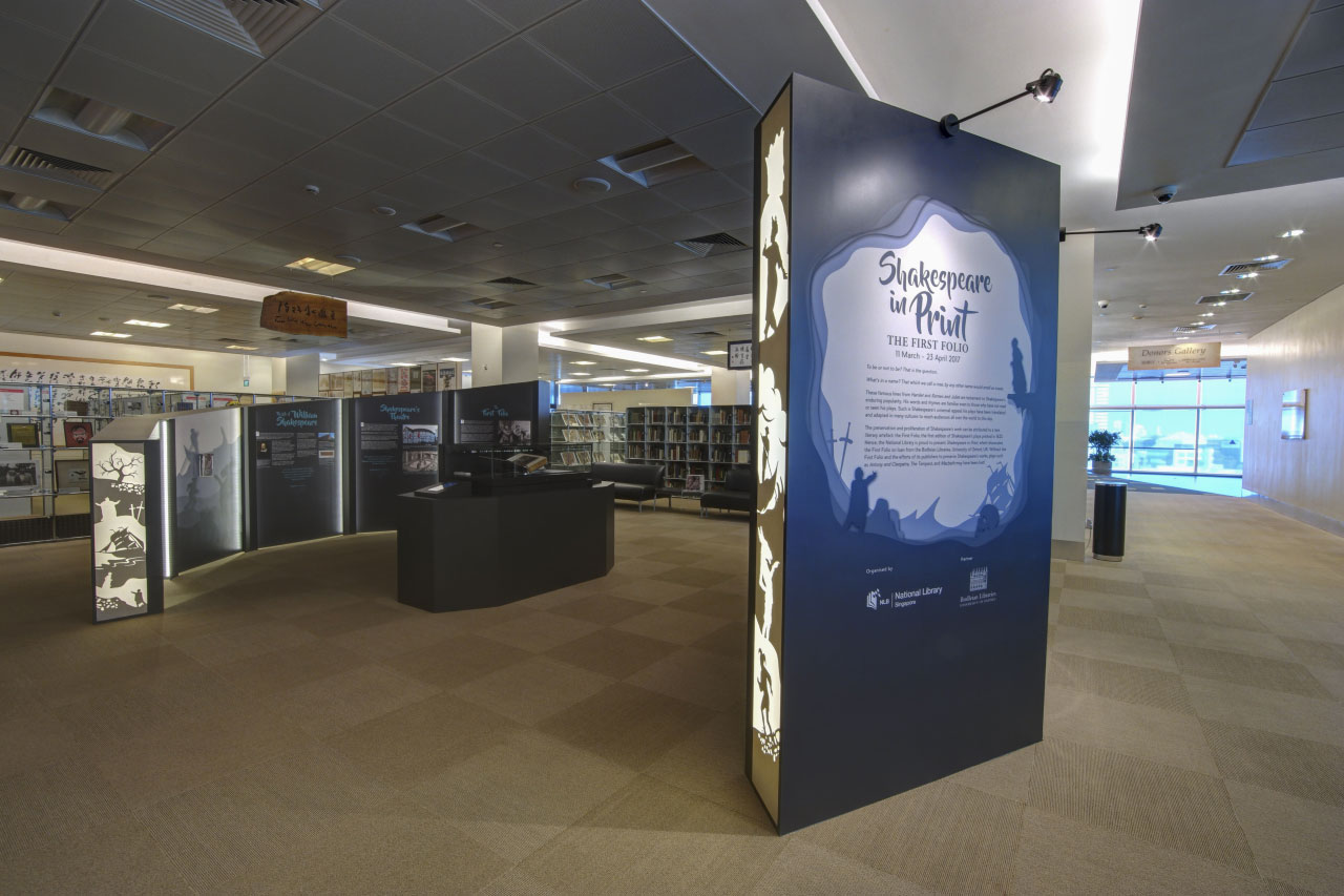 A photo overview of the exhibition. The First Folio lies in the showcase in the middle, surrounded by informational walls.