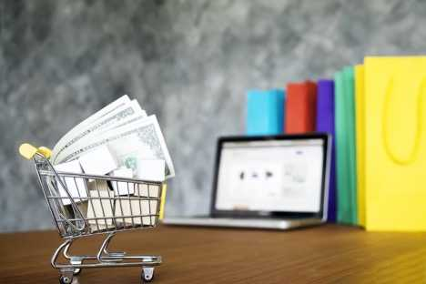 Photo of Small Toy Shopping Cart with Money inside and a laptop in the background.