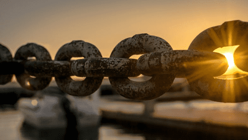 A large metal chain suspended horizontally against a sunset background represents the blockchain subject matter.