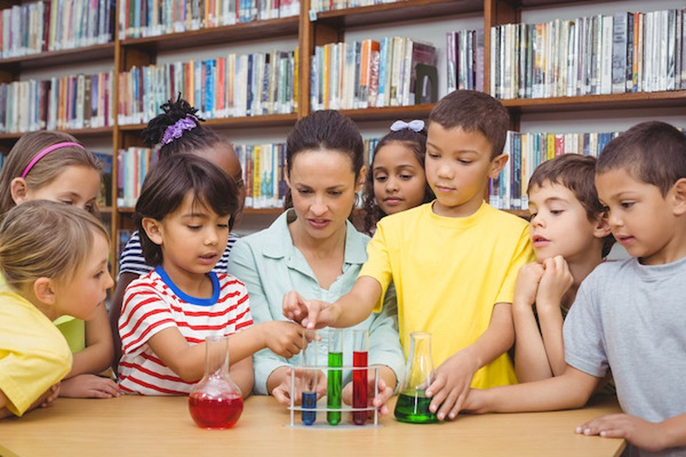 A woman and a group of children doing chemistry experiments