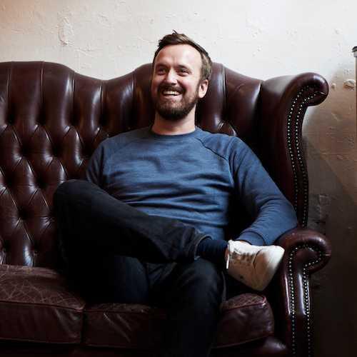 Matt Studdert sitting on a dark burgundy leather sofa