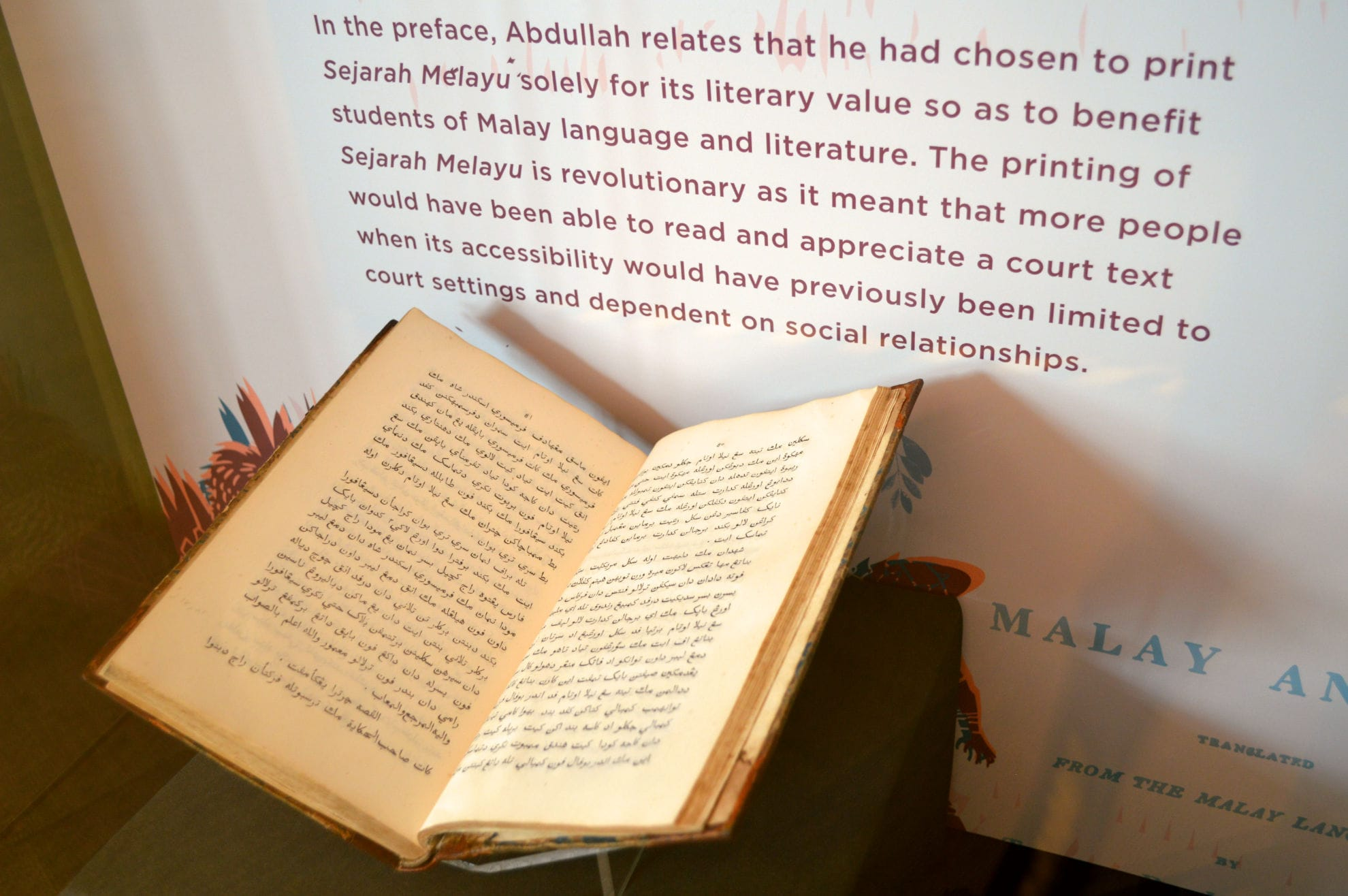 A photo close-up of an opened book within a tall showcase. It contains Jawi script. In the showcase background, there is a printed graphic with a write-up about Sejarah Melayu on it.