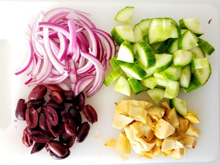 Cut up cucumber, red onion, artichoke hearts, and kalamata olives