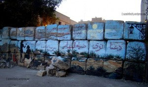[Alaa Awad's mural captured at sunset. Behind the wall, barbwires and idle military policemen fill the empty space]