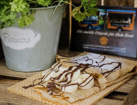 süßer Crepe, gefüllt mit Nutella-Banane, serviert auf nachhaltigem, essbarem Waffelteller