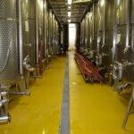 Autoclavi per la produzione del vino poggiate su di una pavimentazione in resina ad uso alimentare.
