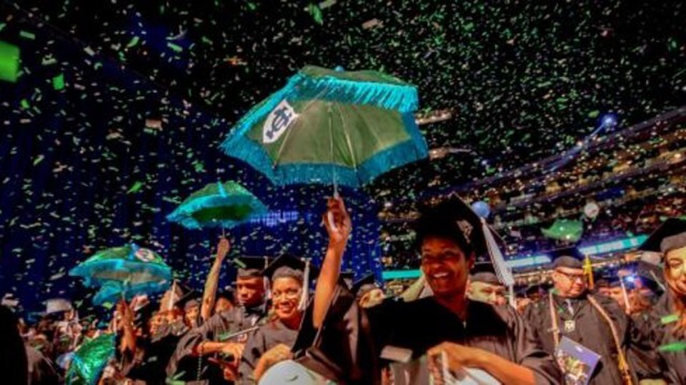 A line of people holding a umbrella with Tulane University's logo dressed with a graduation cap. There's paper falling all over them.