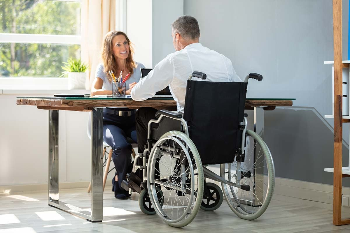 Man in wheelchair sitting at a table having a home assessment with an Occupational Therapist