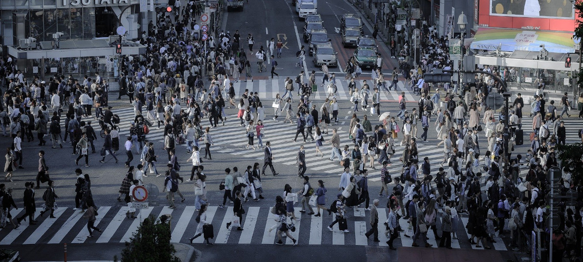 A busy intersection with people walking across in every possible direction