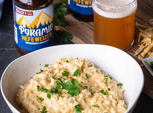 Bowl of Hearty Hefeweizen And Gouda Risotto with a bottle and glass of Pyramid Hefeweizen