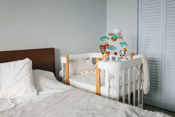 baby wiegje die naast het bed staat