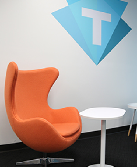 Orange chair with the Trilogy company logo on the wall above it