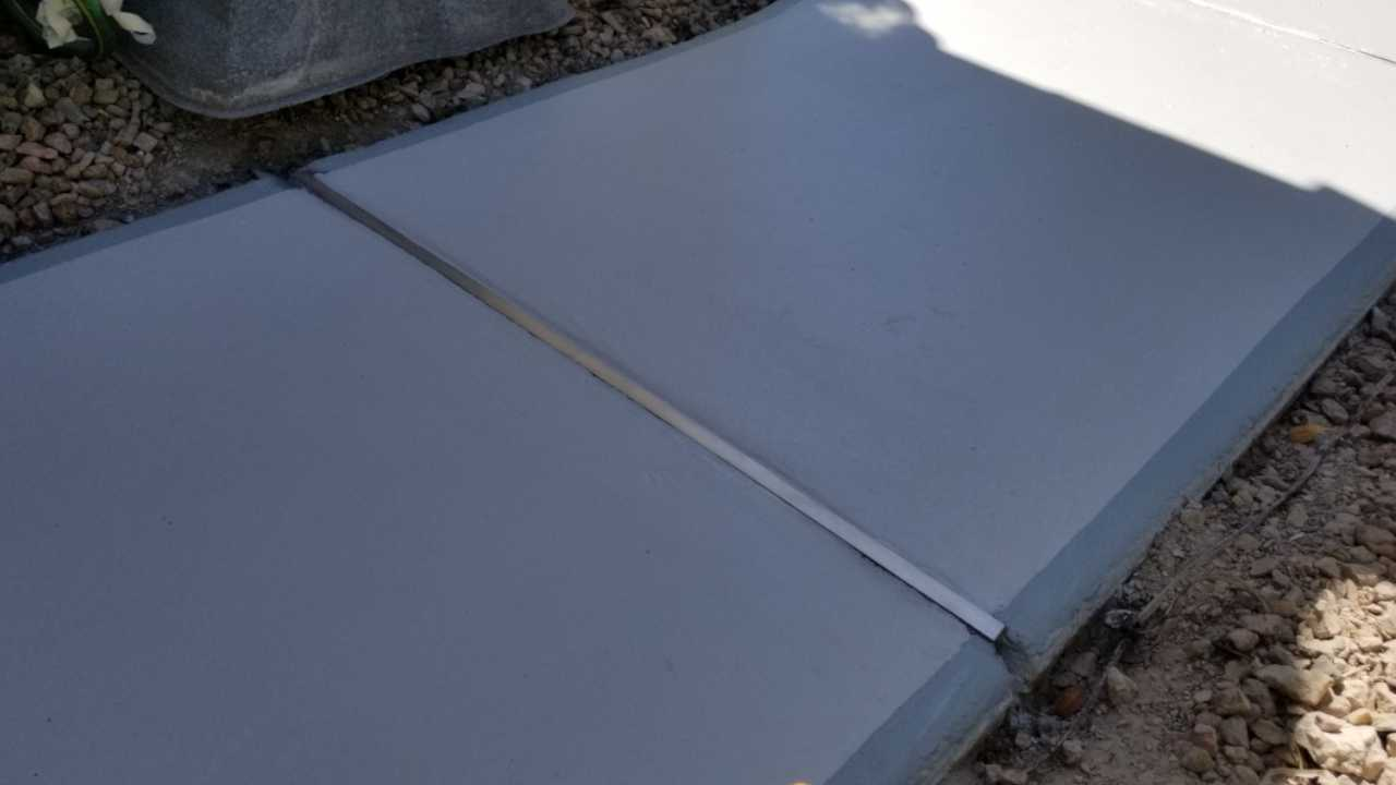 Closeup shot of walkway concrete with custom concrete separation joints after resotoration