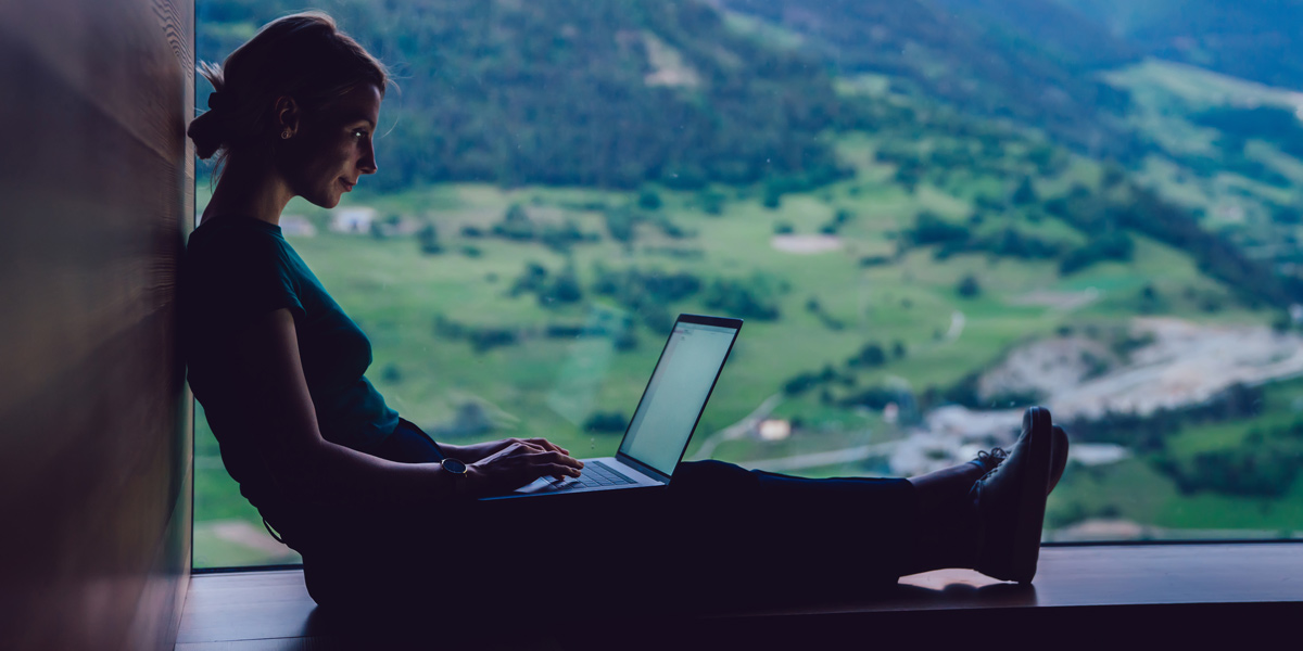 UI designer sitting on a ledge holding a laptop in the countryside