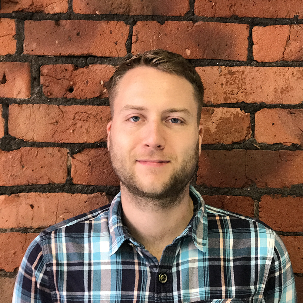 Dan Furze profile photo, wearing a blue checked shirt against an exposed brick wall.