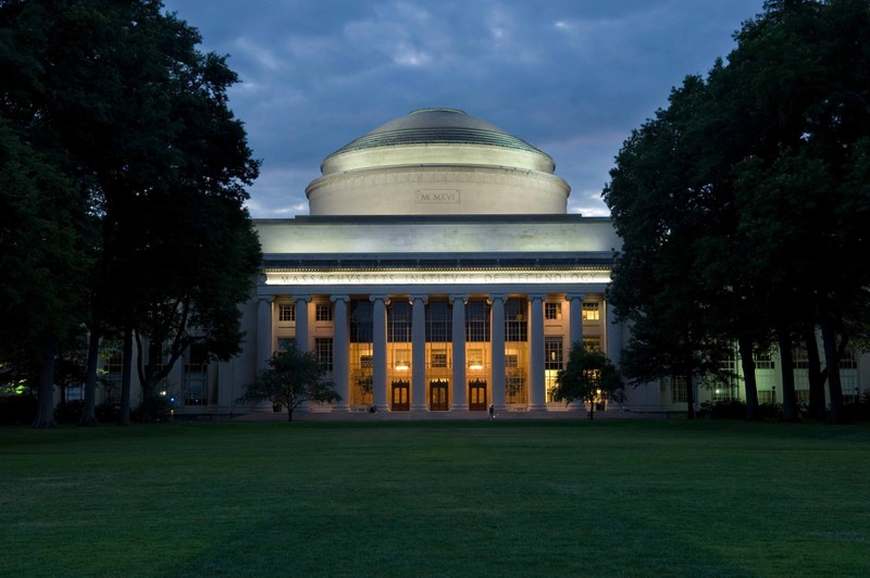 Trees and a grassy quad line the entrance to the Great Dome at MIT
