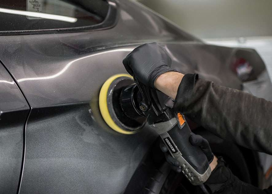 Grey Mustang GT car being machine polished in gloves