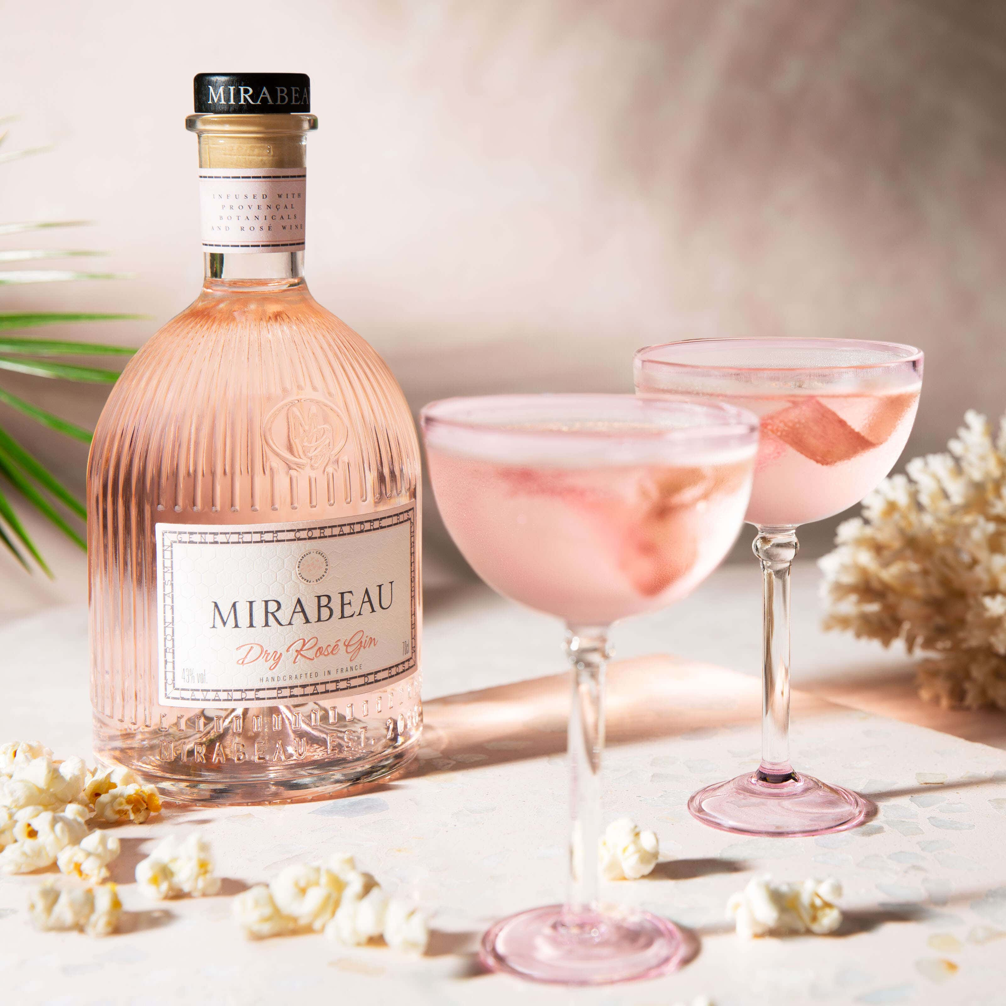 Mirabeau Gin with two cocktails and popcorn on the table with bright sunlight streaming through the images