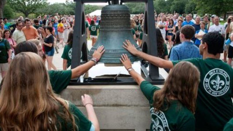 Students wearing a green Tulane University T-Shirt and touching a bell, while a lot of people watch