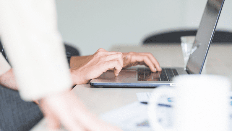 a woman in a blazer leans with two hands on a white desk next to a coffee cup, some paper and a woman typing on a laptop to show why you can say goodbye to excel spreadsheets with futrli, xero and quickbooks integrations with Futrli #integration