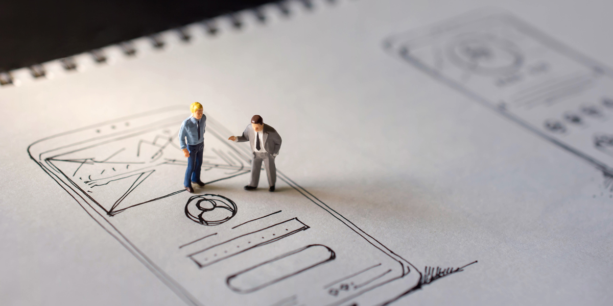 Two miniature figurines standing on top of a hand-drawn wireframe