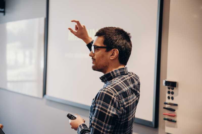 Dekorativt bilde. En mann som står foran en whiteboard og gestikulerer.