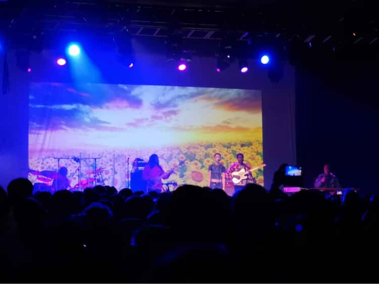 The band, The Internet, performing on stage in Manchester in front of a sunflower background.