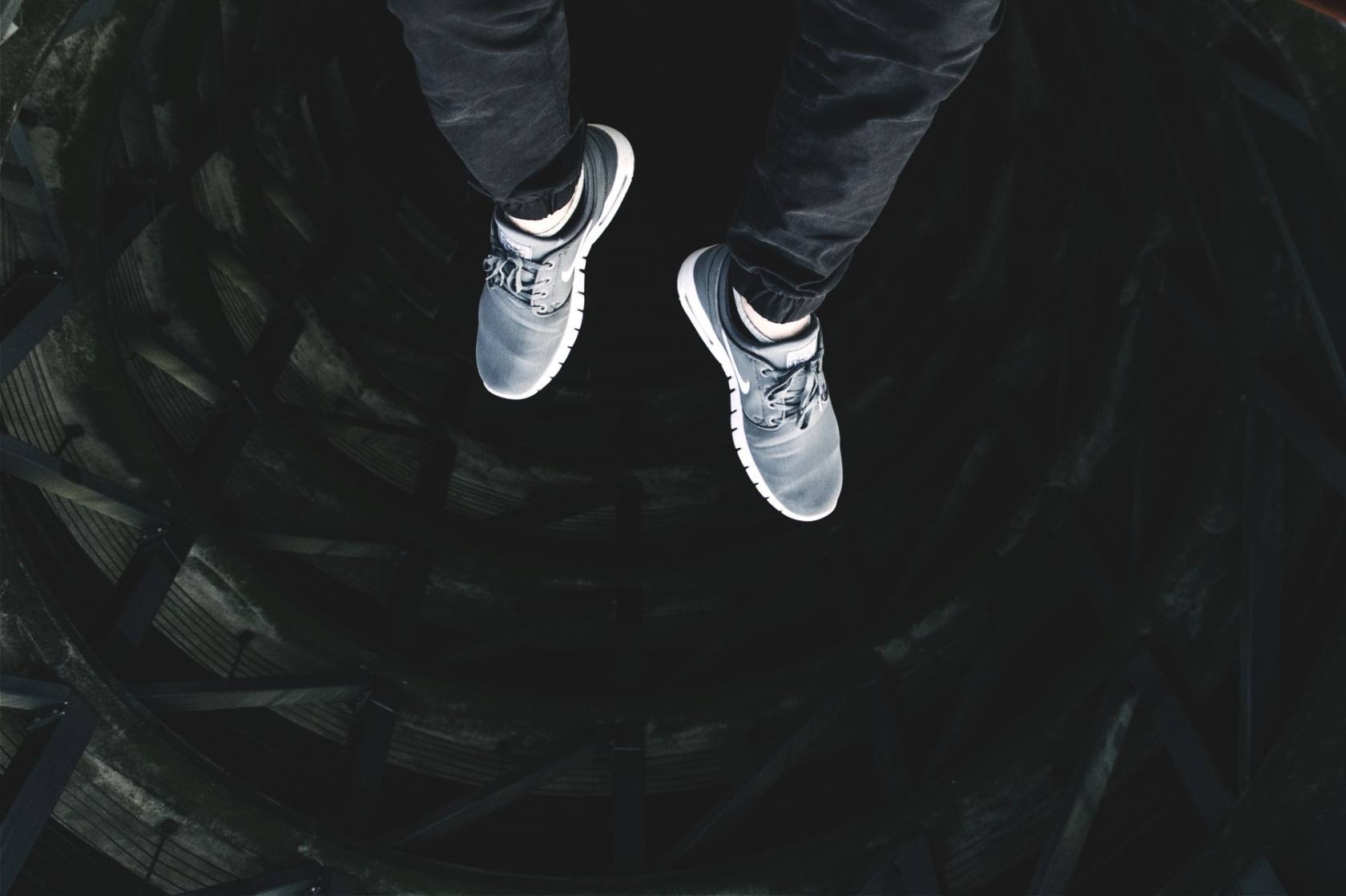A man's feet, looking down from the top of a building