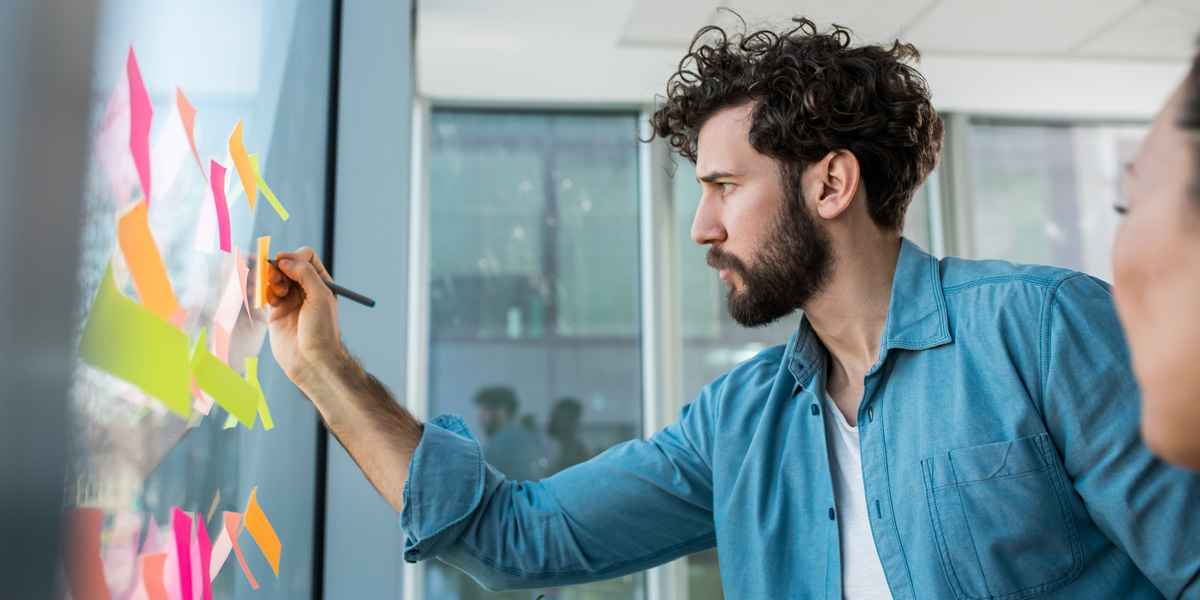 A UX designer in side profile, placing sticky notes on a window