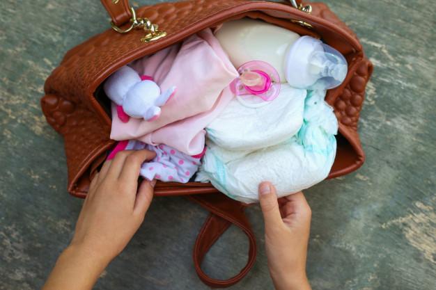 Madre preparando bolso del bebé
