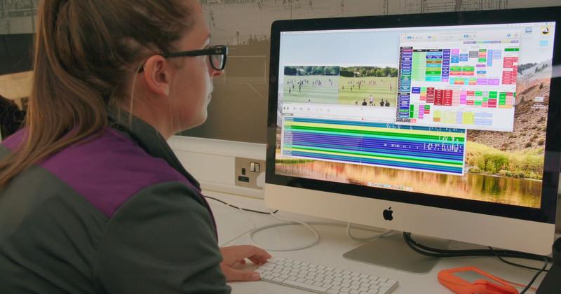 コンピューターで試合を分析する女性