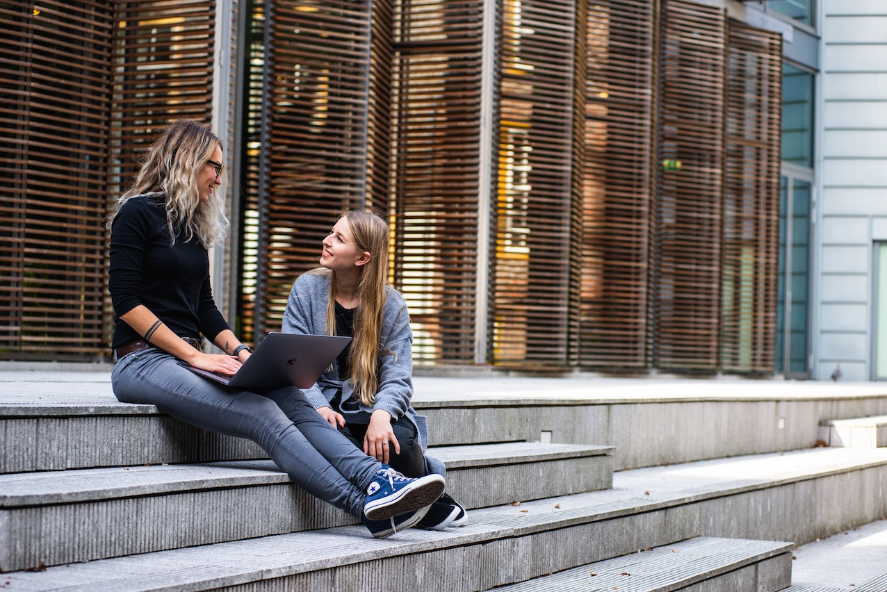 Students sitting on a step outside a university.