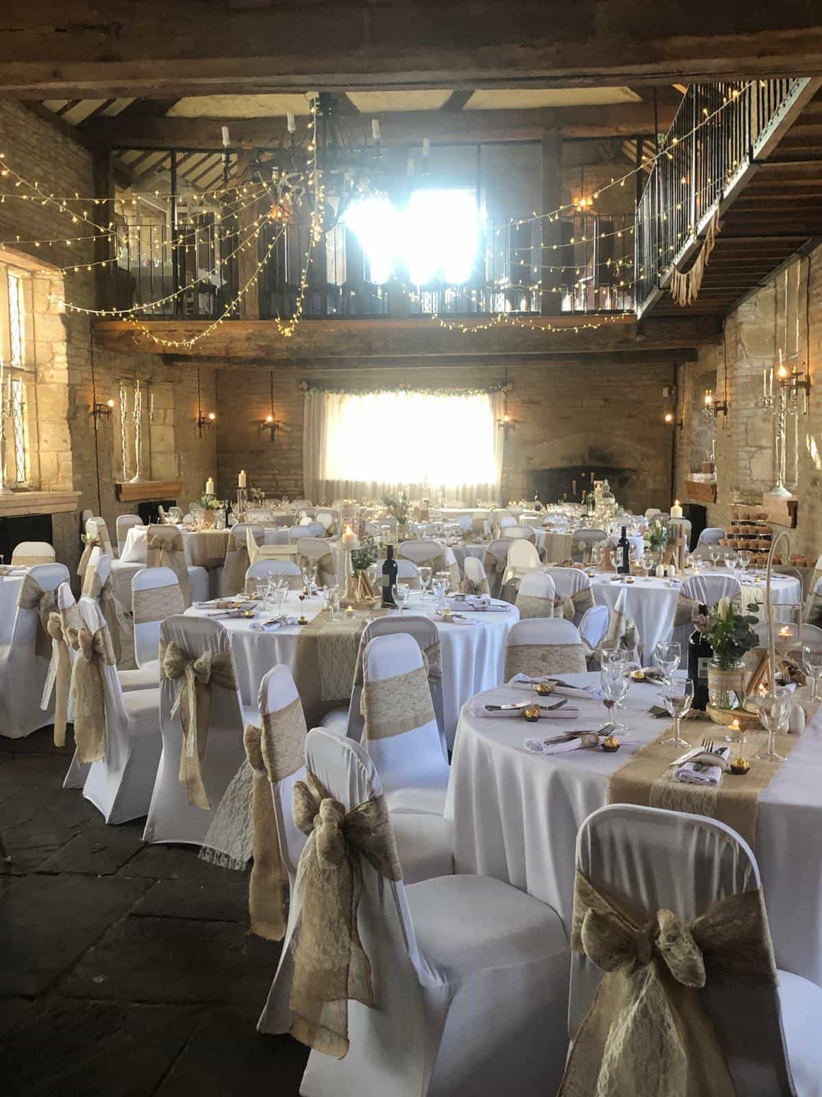 beautiful white table and chair linens highlighted by gold hessian sashes and twinkling golden starlights around the room