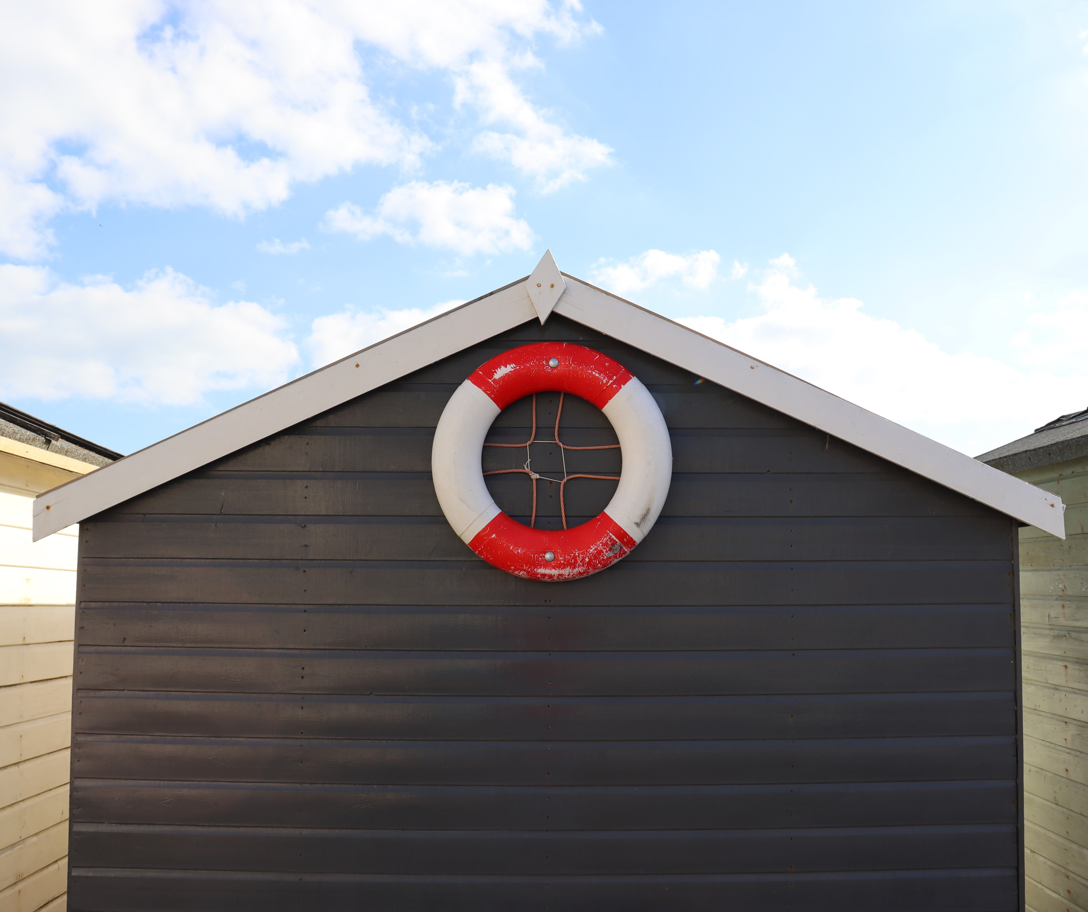 A grey beach hut with a white roof that has a red and white life ring attached to it.