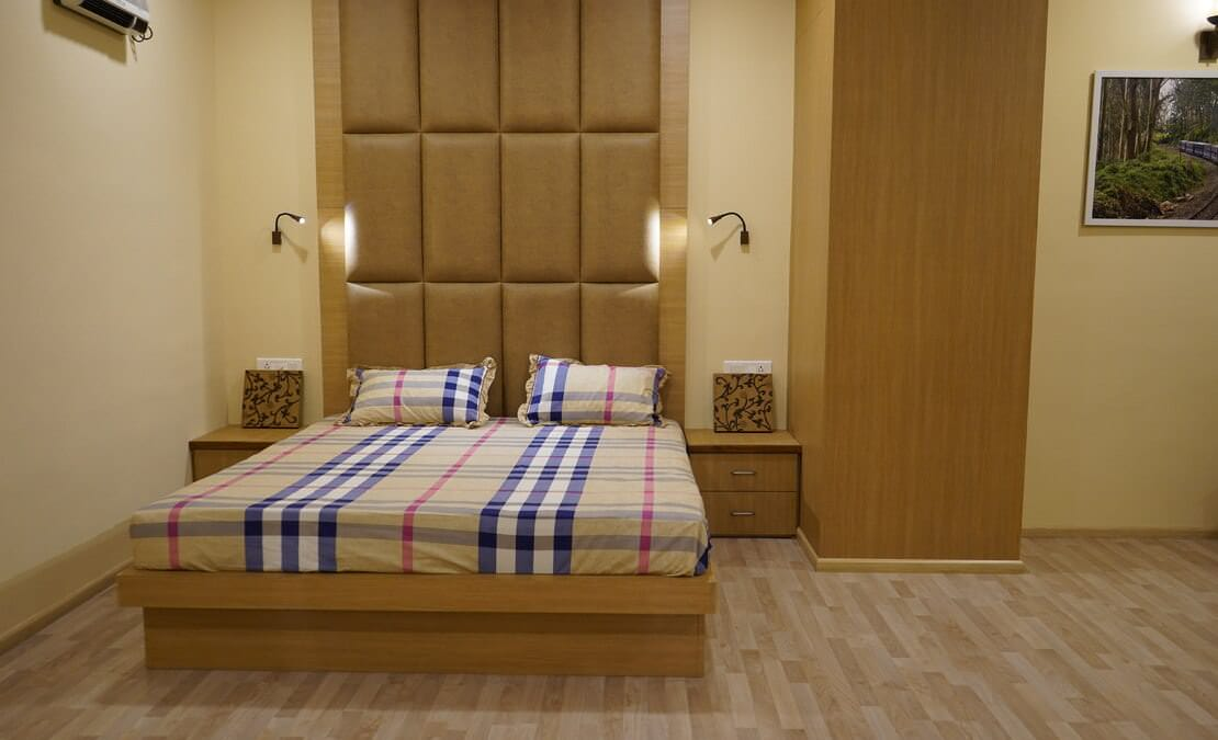 Streamside Duranta bedroom with wooden flooring and bed