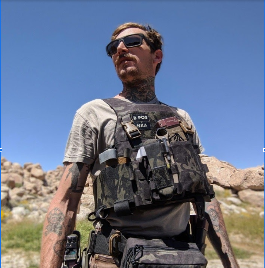 A man poses in the desert with body armor and a handgun in a holster on his leg.
