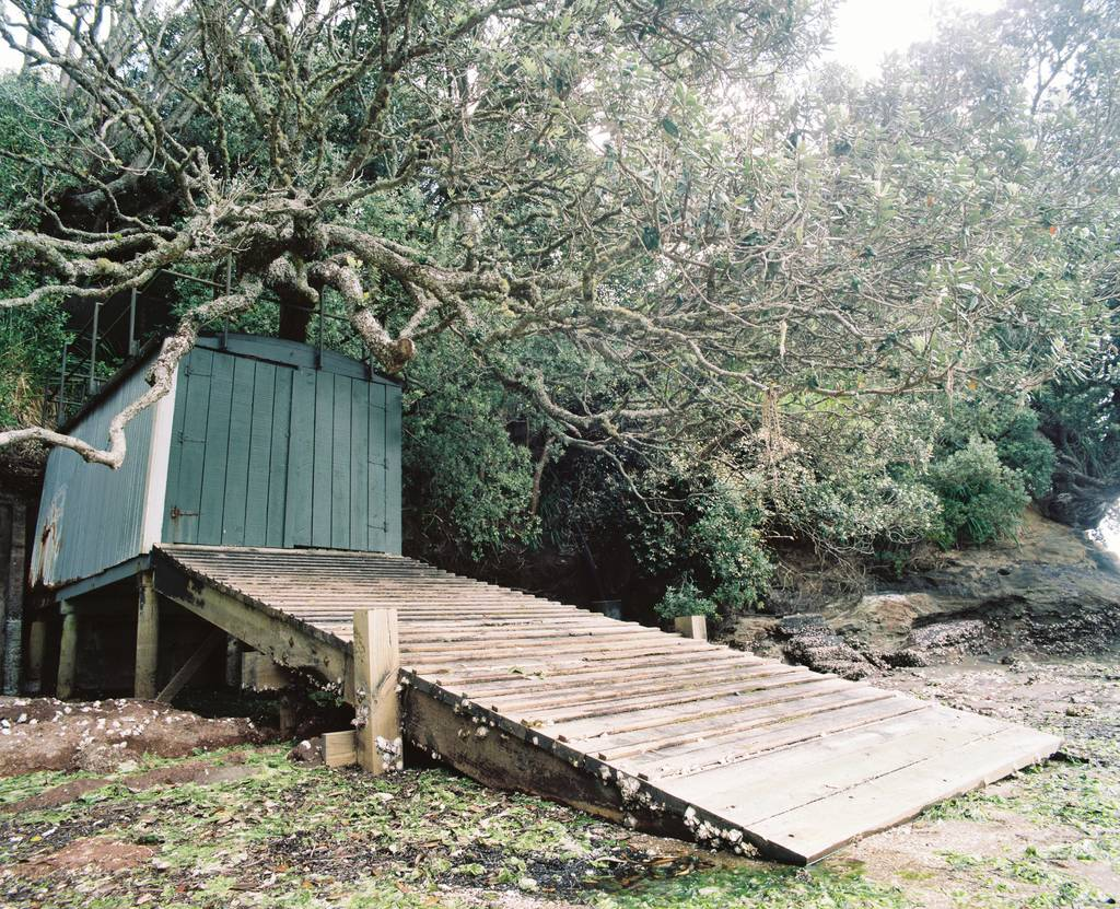A boathouse under a tree nestled between the rocks