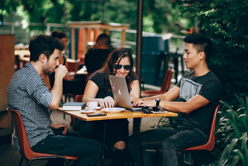Three students sitting outside at a coffee shop studying